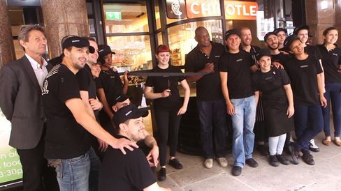 Staffers gather outside Chipotle's new London restaurant for a ribbon-cutting ceremony.