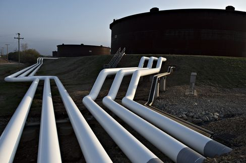 Pipelines run toward oil storage tanks stand at the Enbridge Cushing storage terminal.