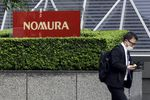 """A pedestrian wearing a protective face mask walks past the Nomura Holdings Inc. signage outside its headquarters in Tokyo, Japan, on Monday, March 29, 2021. Nomura's warning of a """"significant"""" potential loss from an unnamed U.S. client is related to the unwinding of trades by Bill Hwangs Archegos Capital Management, according to people familiar with the matter."""