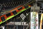Train cars lay at an angle after a raised subway track collapsed in Mexico City.