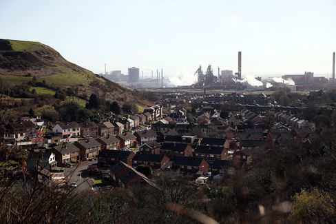 Residential houses stand against a backdrop of the steel works in Port Talbot.