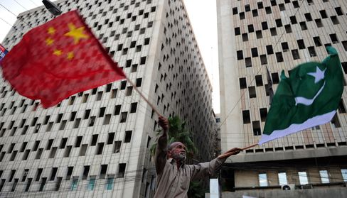 A Man Waves Pakistani and Chinese National Flags in Karachi