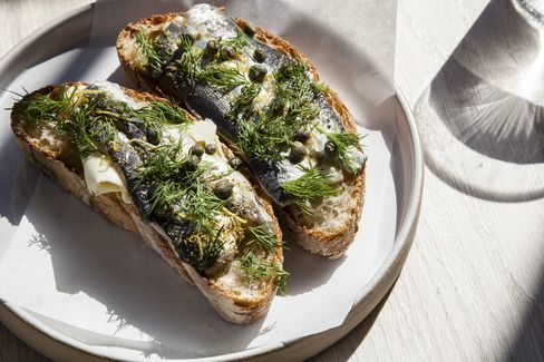 The snack menu is toast-forward and includes cured sardines on buttered bread.