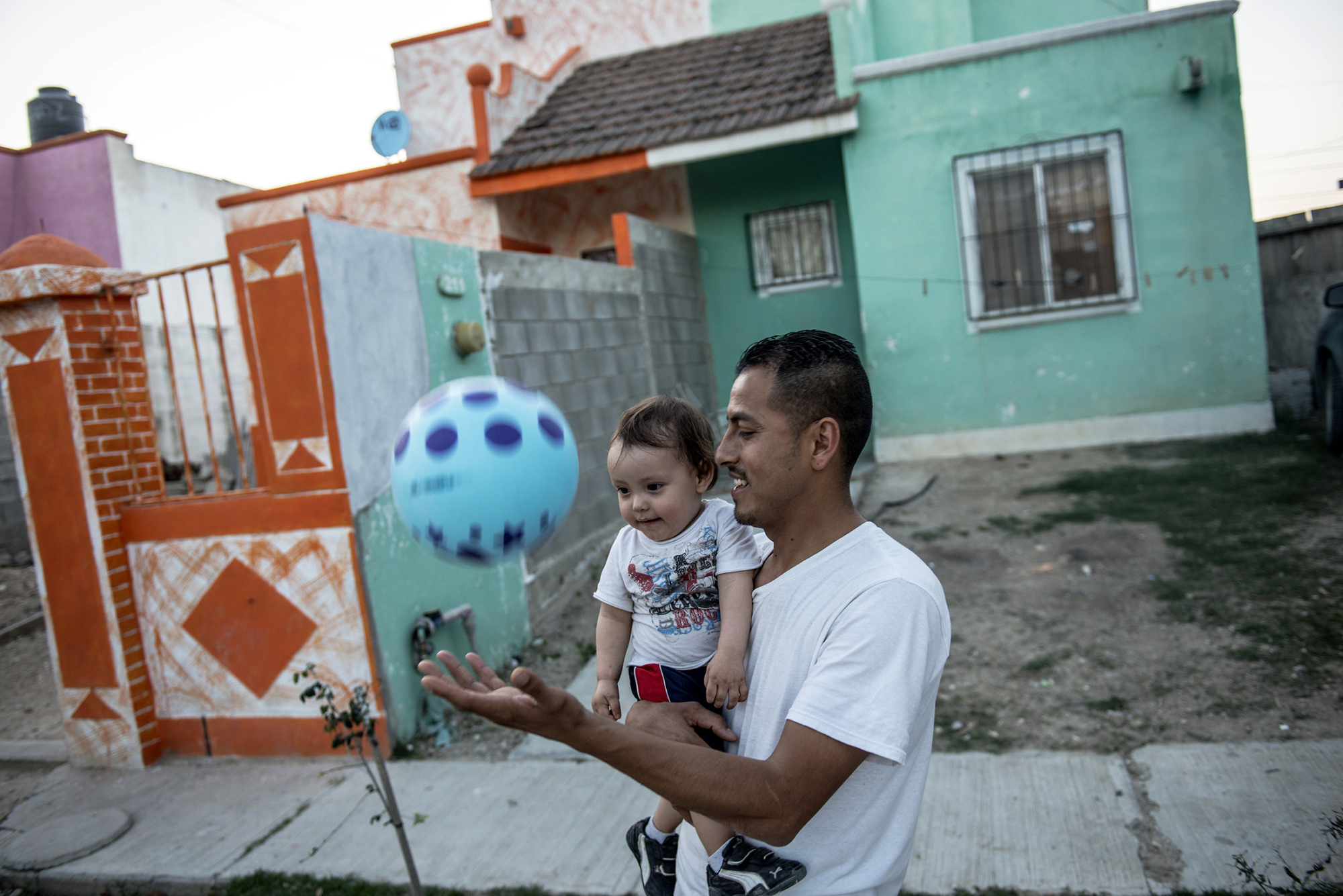 Manuel Aragon plays with his one-year-old son in Acuna, Mexico.
