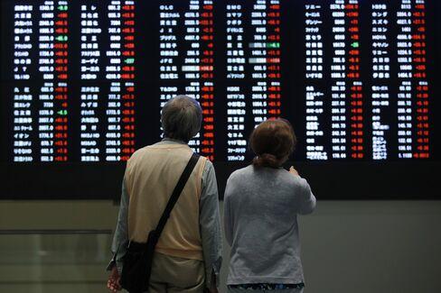 東証内の株価ボードを見る見学者