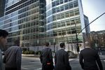 Men cross the street in front of Goldman Sachs Group Inc.'s headquarters in New York, U.S.