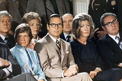 Treasury Secretary William Simon, left, sits with Nancy Kissinger and Secretary of State Henry Kissinger as they listen to former President Nixon talk to his staff prior to leaving the White House for the last time, August 9, 1974.