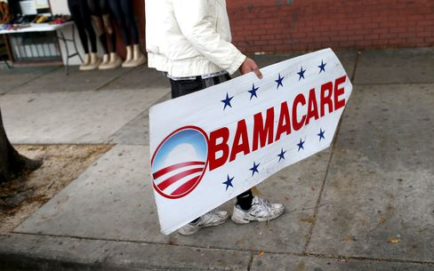 A sign directs people to an insurance company where they can sign up for the Affordable Care Act, also known as Obamacare, on Feb. 5, 2015, in Miami.