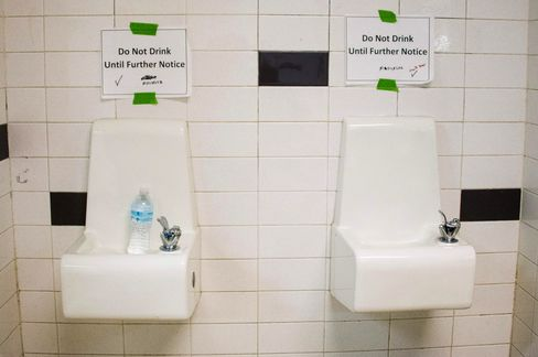Signs above fountains warn against drinking the water at a school in Flint.