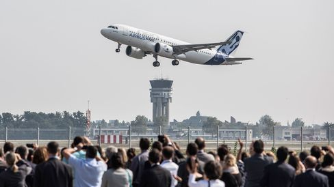 Spectators watch as an Airbus A320neo aircraft manufactured by Airbus Group NV takes off on its debut flight at Toulouse-Blagnac airport in Toulouse, France, on Sept. 25, 2014.