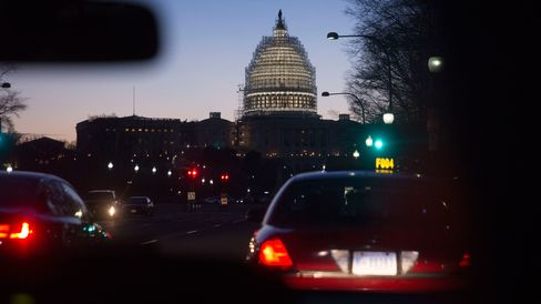 Scaffolding surrounds the U.S. Capitol Building Dome before sunrise, as seen from a taxi, in Washington, D.C., U.S., on Wednesday, Dec. 10, 2014.