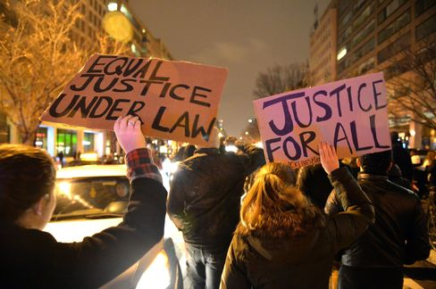 Protesters march holding banners in downtown Washington DC on December 05, 2014 during the third night of nationwide protests, after a grand jury decided not to charge a white police officer in the choking death of Eric Garner, a black man, days after a similar decision sparked renewed unrest in Missouri. Eric Garner died after being placed in a chokehold by New York police Officer Daniel Pantaleo while being arrested on suspicion of selling untaxed cigarettes in Staten Island