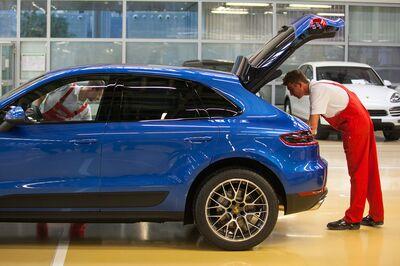 Employees check a Porsche Macan sport-utility vehicle (SUV) inside the Porsche AG factory in Leipzig.