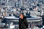 This picture taken on January 19, 2021 shows the National Stadium (back), the main venue for the Tokyo 2020 Olympic and Paralympic Games, as a visitor (front) stands at the Shibuya Sky observation deck in Tokyo. - When the Tokyo Olympics were postponed last year, officials promised they would open in 2021 as proof of humankind's triumph over the coronavirus. But six months before the delayed start, victory over the virus remains distant, and fears are growing rapidly that the Games of the 32nd Olympiad may not happen at all. (Photo by Philip FONG / AFP) / TO GO WITH AFP STORY OLY-2020-2021-JAPAN-VIRUS-HEALTH BY ANDREW MCKIRDY (Photo by PHILIP FONG/AFP via Getty Images)