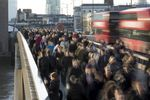 Commuters walk across London Bridge in London, U.K., on Monday, Dec. 18, 2017. U.K. firms wanting workers face the tightest labor market in two decades. In 2011, there were almost six unemployed people for every vacancy; now there are fewer than two, the lowest ratio since records began in 2001.