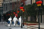 Volunteers in isolation gowns walk to send groceries to residents in home quarantine in Wuhan on Feb. 20.