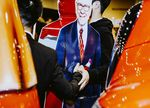 Attendees take pictures with a cardboard cutout of Warren Buffett during the Berkshire Hathaway annual meeting.