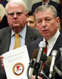 Former U.S. Attorney General John Ashcroft (right) holds up a copy of a Justice Department Patriot Act report during a news briefing with Representative James Sensenbrenner in 2004