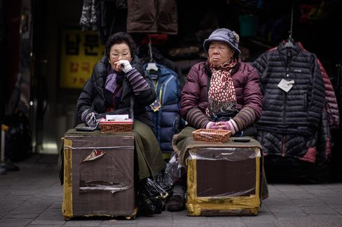 Currency exchange vendors at a market in Seoul.