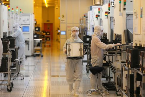 Employees dressed in dustproof clothing work at the plant of Semiconductor Manufacturing International in Beijing.