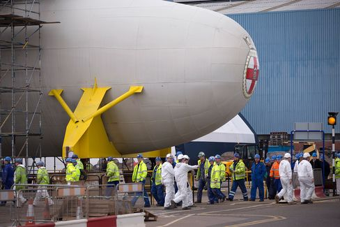 Workers pass the bulbous bow section of the Royal Navy's second Queen Elizabeth class aircraft carrier, the Prince of Wales, manufactured by the Aircraft Carrier Alliance, a joint operation between BAE Systems, Thales SA and Babcock International Group Plc, at Babcock shipyard in Rosyth, U.K., on March 25, 2014.
