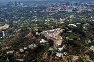 Buildings in downtown Los Angeles stand in the distance as construction continues at a home being built by Nile Niami, a film producer and speculative residential developer, in this aerial photograph taken in Bel Air, California, U.S., on Monday, May 18, 2015. Niami, who hopes to sell the house for a record $500 million, is pouring concrete in L.A.s Bel Air neighborhood for a compound with a 74,000-square-foot (6,900-square-meter) main residence and three smaller homes, according to city records. Photographer: David Paul Morris/Bloomberg