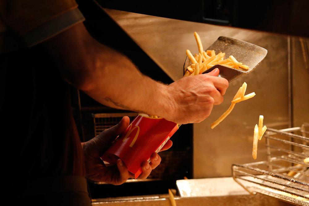 An employee scoops fries into a carton inside a McDonald's Corp. restaurant.