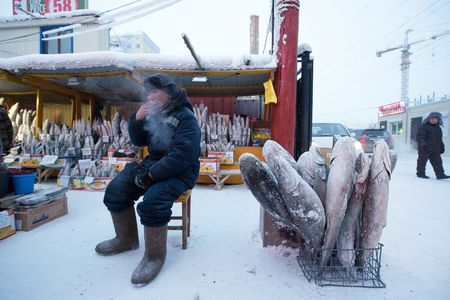 A food vendor smokes a cigarette as he sits beside a basket of frozen fish at the Krestyansky open air market in Yakutsk, Russia.
