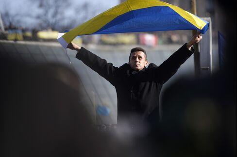 A Man Waves Ukraine's National Flag in Kiev