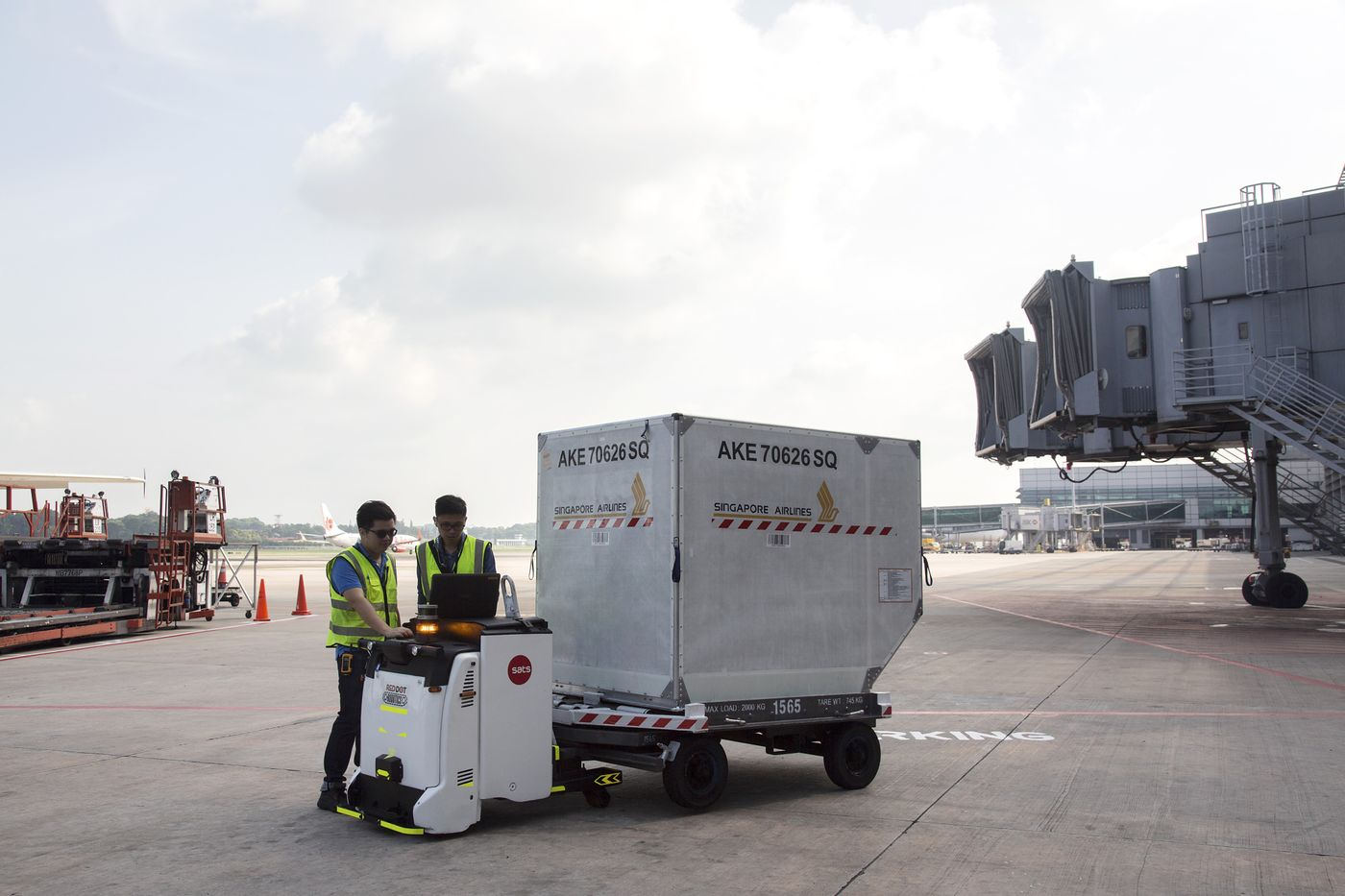 An Autonomous Container Trailer (ACT) baggage robot on the tarmac at Changi Airport. Photographer: Ore Huiying/Bloomberg