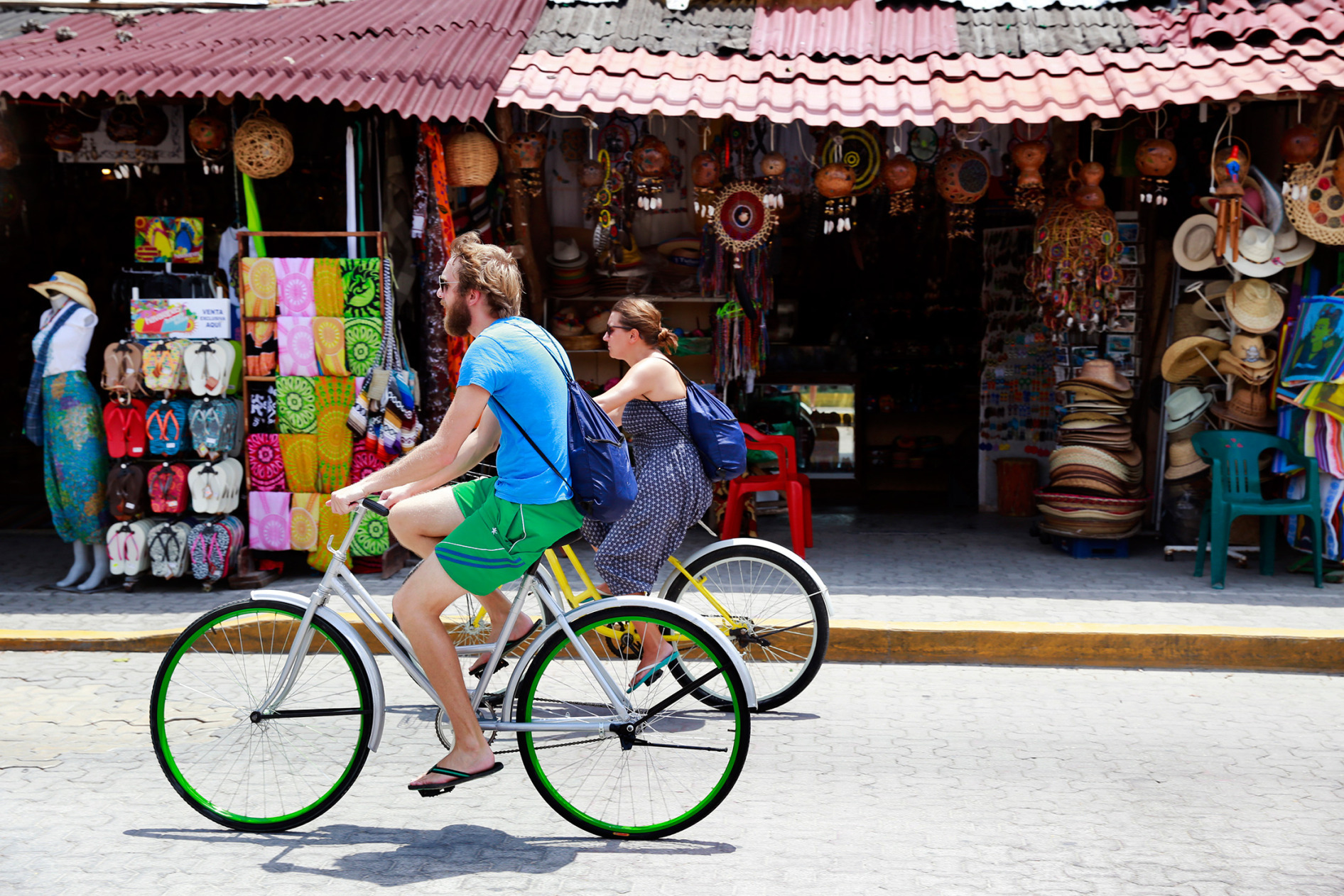 Visitors bike past shops in downtown Tulum, Mexico.
