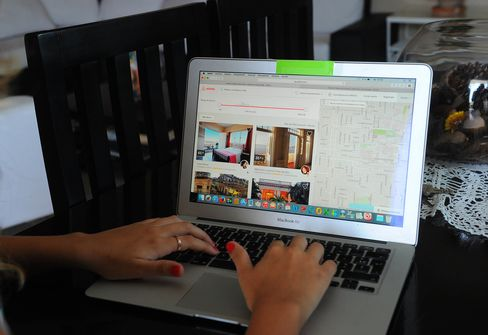 A Cuban woman provides an Airbnb reservation service from a laptop in a rental house in Havana.