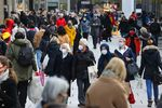 Shoppers wear protective face masks on a crowded retail high street in Frankfurt, Germany, on Monday, Dec. 14, 2020.
