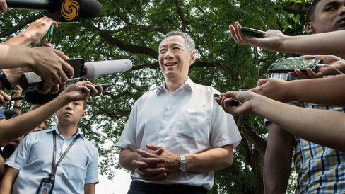 Lee Hsien Loong, Singapore's prime minister and leader of the People's Action Party (PAP), center, speaks to the media after voting at a polling station in Singapore, on Sept. 11, 2015.