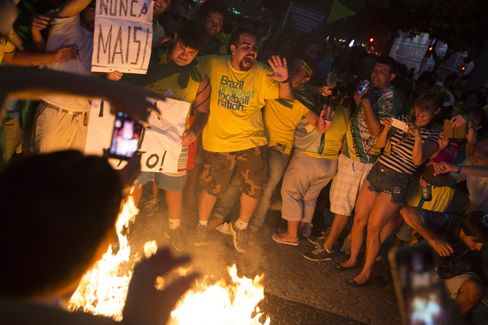 Protesters burn a figure in Rousseff's likeness.