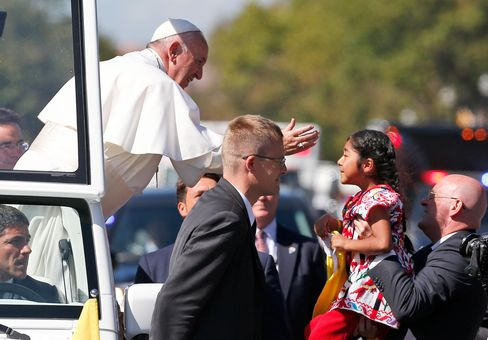 Pope Francis reaches from the popemobile to greet a child during a parade in Washington on Sept. 23, 2015.