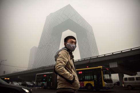 A man wears a mask as he waits to cross a road near the CCTV building during heavy smog on Nov. 29, 2014, in Beijing.