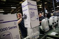 An employee assembles boxes of dehumidifiers on the production line at the Ebac Ltd. factory in Newton Aycliffe, U.K.