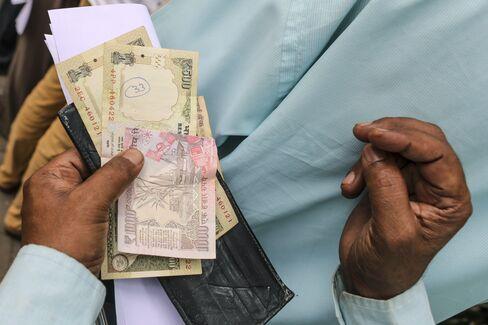 500ルピーと1000ルピー札を持つ男性