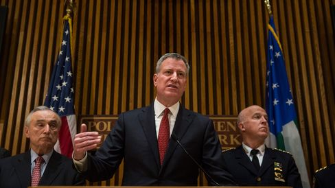New York City Mayor Bill de Blasio (C) and New York Police Department Commissioner Bill Bratton (R) speak at a press conference.