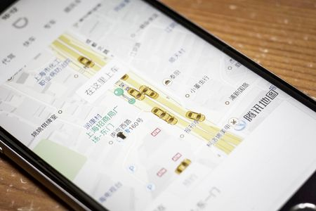 The Didi Chuxing application is displayed on a smartphone screen in this arranged photograph taken in Shanghai, China, on Sunday, May 22, 2016. Philippe Laffont's Coatue Management LLC, which manages more than $7 billion, has backed China's biggest ride-hailing app Didi Chuxing as it competes with Uber Technologies Inc. Photographer: Qilai Shen/Bloomberg