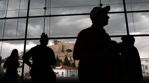 Visitors pass a view of the Acropolis Hill as they walk through the Acropolis museum in Athens.