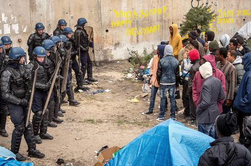 Police officers and gendarmes proceed with operations during the eviction of around 200 Syrian refugees from a camp site in Calais, northern France, on September 21, 2015.