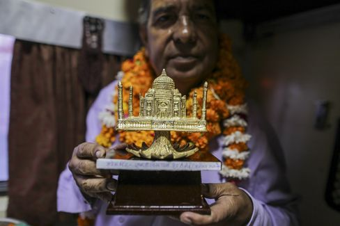 Jamil Ahmad, 60, chief ticket collector, displaysa gift on his retirement day as Kalka Mail train stands at Tundla junction in Tundla, India.