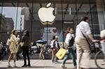Pedestrians walk past an Apple Inc. store in Shanghai, China.