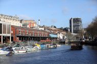 Boats sit moored on the harborside as a river ferry passes by in Bristol, U.K.