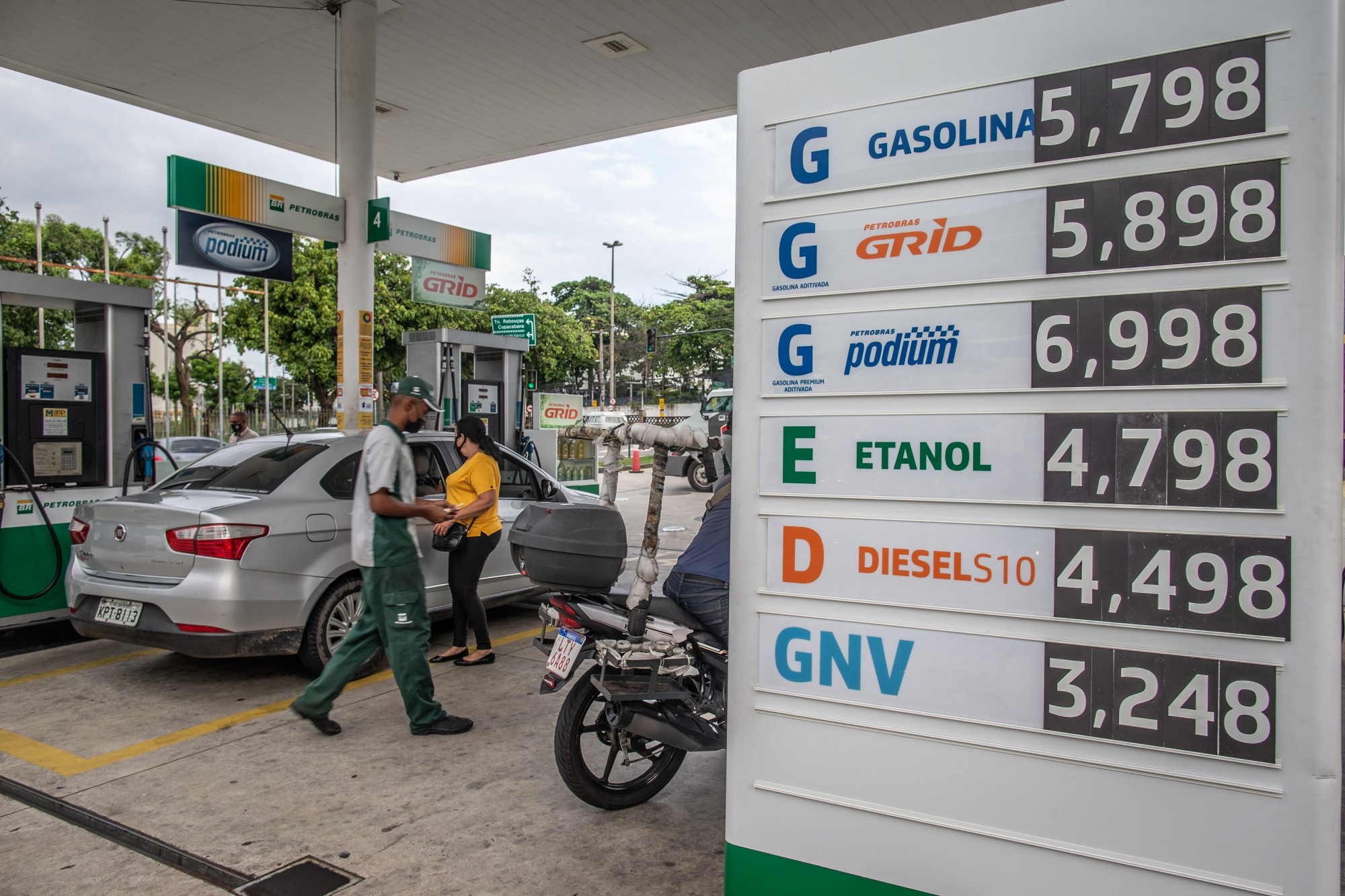 Workers fuel vehicles at a Petrobras station in Rio de Janeiro.