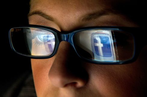 FILE: In this file photo the Facebook Inc. logo is reflected in the eyeglasses of a user in this arranged photo in San Francisco, California, U.S., on Wednesday, Dec. 7, 2011. A Facebook IPO would provide funds to help the social-networking service maintain its expansion and fend off competition from Internet rivals such as Google Inc. and Twitter Inc. Photographer: David Paul Morris/Bloomberg