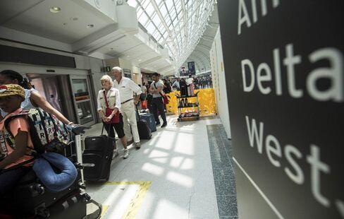 Passengers wait to board a Delta flight