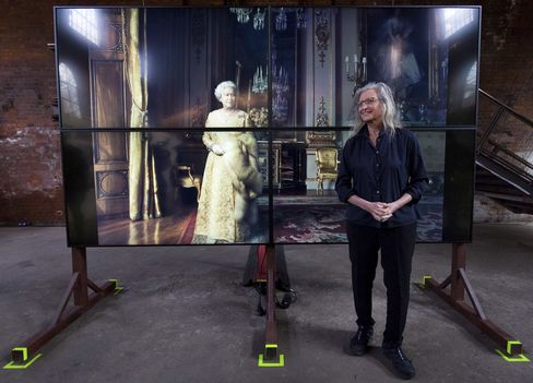 Leibovitz poses in front of a photograph of Britain's Queen Elizabeth II during the exhibition opening.